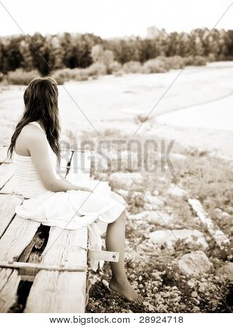 Young woman sitting on old wooden surface, sepia toned.
