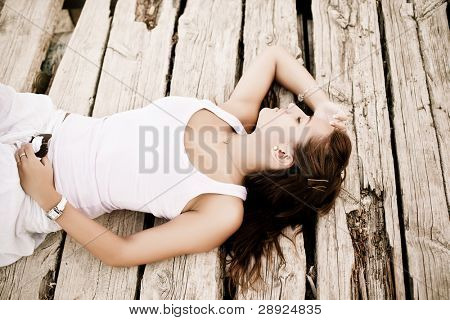 Young woman laying over wooden surface