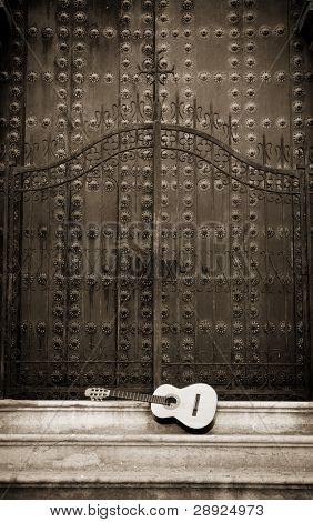 Spanish guitar in front of a cathedral doors