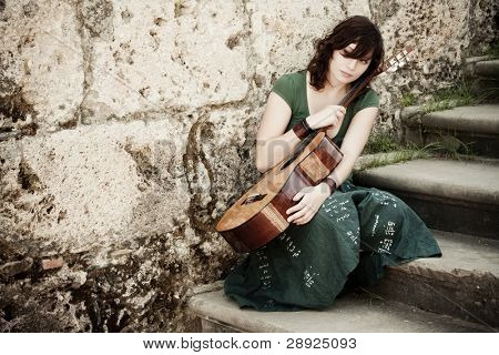Young female guitarist on antique background