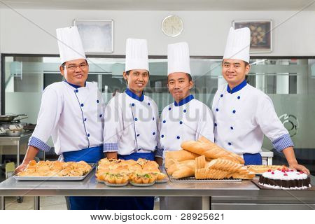 Chef or bakers posing in front of the bread, pizza and tart in commercial kitchen