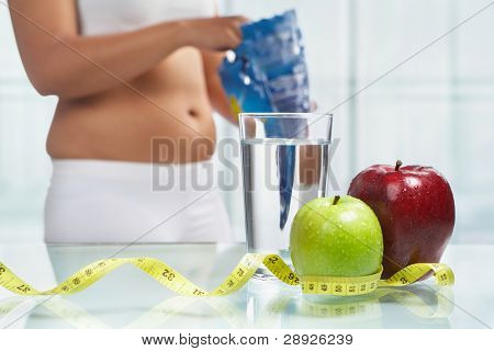 Apples and water with measuring tape on table with female body on sport attire at background eating snack, shot for diet concept