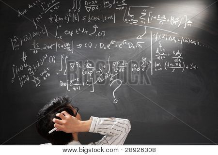 Looking at difficult complex mathematics equation on balckboard