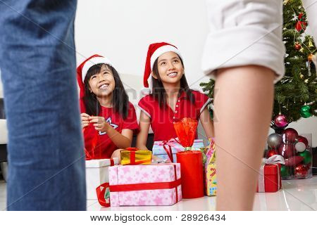 Kids busy opening Christmas present while parents approaching