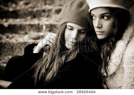 Portrait of two sad girls, dark sepia toned.