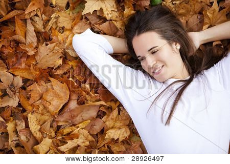 Young beautiful happy girl over autumn sheet.