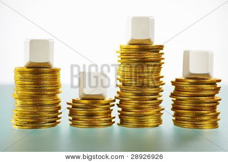 Four blank block over stack of gold coins showing up and down bar