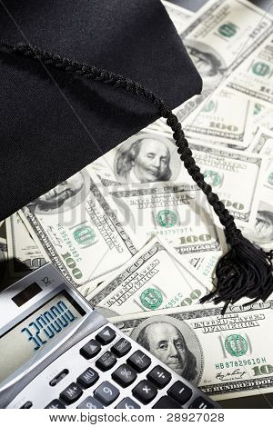 Graduation hat, and diploma certificate on top scattered US dollar bills for expensive education concept