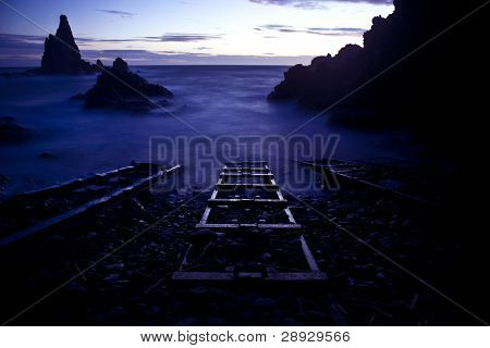 Surreal scene, three railroads straight into the ocean.