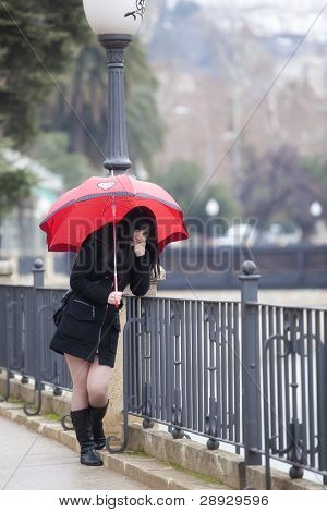 Sad girl with red umbrella on urban background.