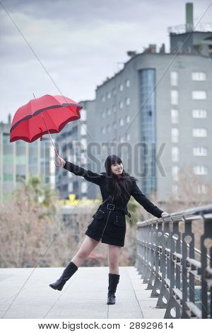 Young happy girl dancing under rain