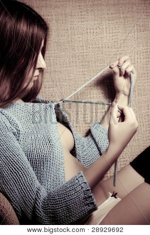 Young beautiful woman undoing her cardigan.