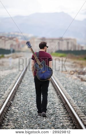 Young male musician walking with his acoustic guitar.