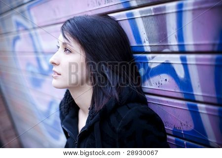 Young beautiful teen in pensive gesture in street background.