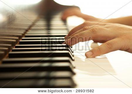 Manos sobre el piano en tonos cálidos.