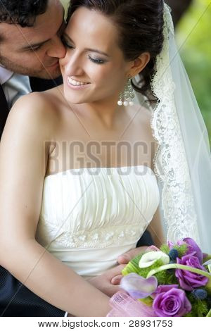 Groom kissing bride on their wedding day.