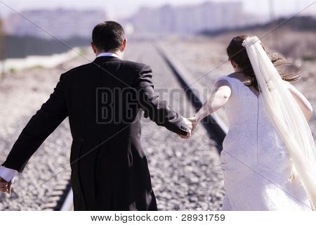 Unrecognizable just married pareja corriendo