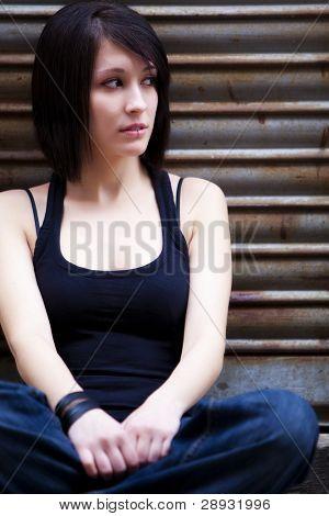 Bela jovem sentado no fundo urbano