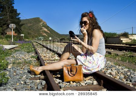 Young woman missed her train and put on lipstick while she waits for the next one