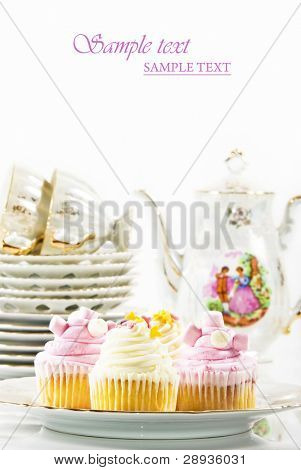 Lovely cupcakes on a plate with plates, cups and teapot ready for party