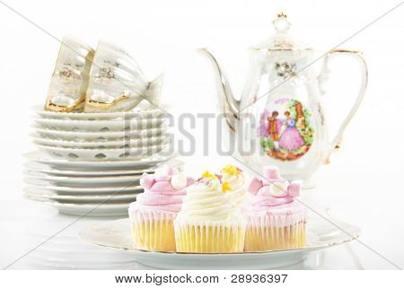 Cupcakes on a plate with cups and saucers and teapot