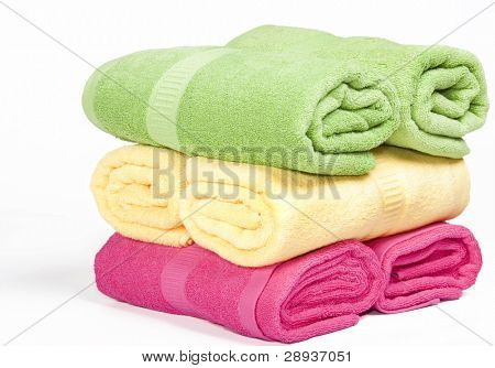 Green, yellow and pink towels stacked up on a white background