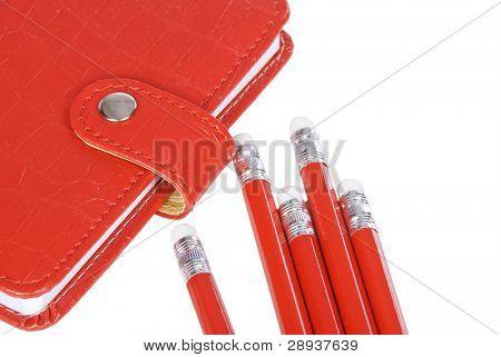 un cuaderno rojo con lápices rojos sobre fondo blanco - listo para estudiar