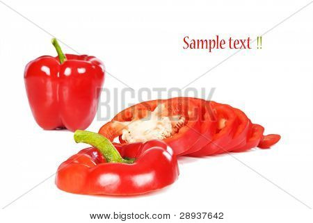Red sweet peppers - one whole and one cut in rings - on a white background with space for text
