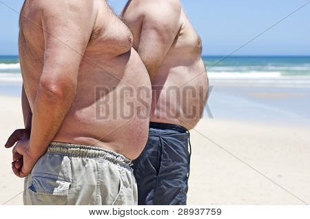 Two very fat men on the beach