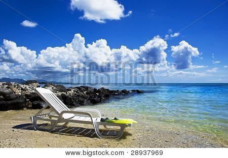 a Beach chair with diving shoes on a tropical island beach