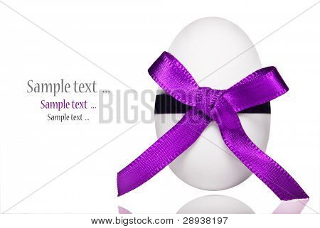 a White candy coated easter egg with a bright purple ribbon on a pure white background with space for text