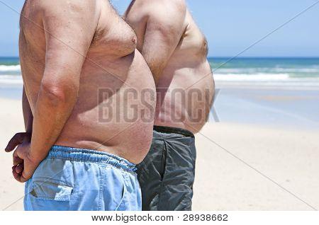 Close-up de dois homens gordos mostrando sua barriga na praia