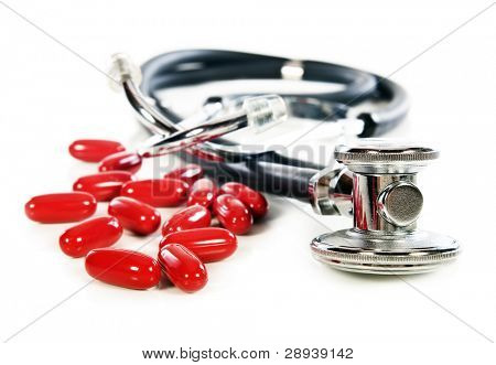 a Doctor's stethoscope   and red pills on a white background with space for text