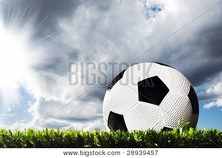 Close up of a soccer ball on a soccer field ready for kick off - under heavy clouds with sun breaking through