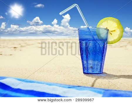 Close up of a blue glass with sparkling water and lemon on a beach