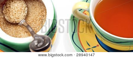 Close up of a cup of wholesome healthy green tea and a bowl of brown sugr