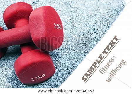 a Pair of red dumbbells on a blue towel with space for text