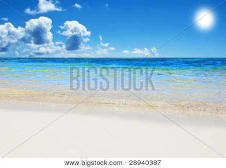 An open tropical island beach with sky and clouds