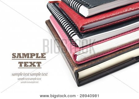 Multiple books stacked up - close up on a white background with space for text