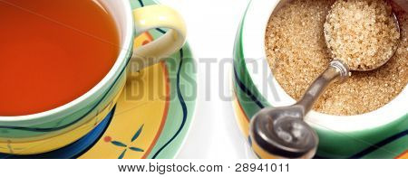 Close up of a cup of wholesome healthy green tea and a bowl of brown sugar