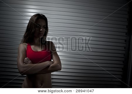 Fitness Trainer In Dark With Arms Folded