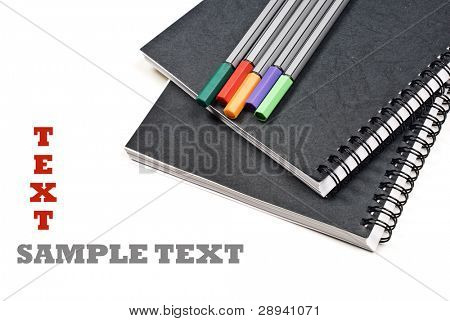 Black note books and colorful pens on a white background with space for text