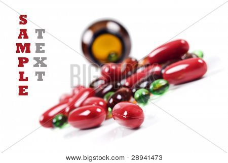Colorful pills spread in front of a pill bottle.
