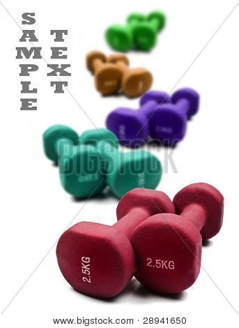 Different colored dumbbells on a white background with space for text