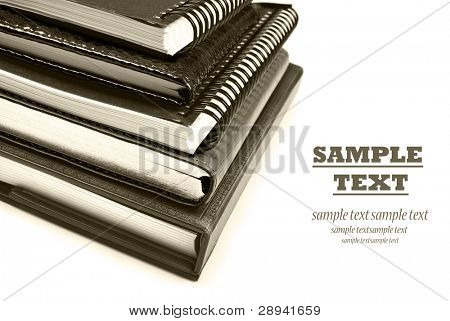 Sepia photo of stacked up books - close up on a pure white background with space for text