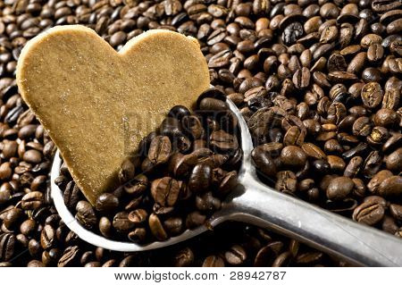 Heart shaped cookie in a scoop of coffee beans  - intentional low light and shallow depth of field