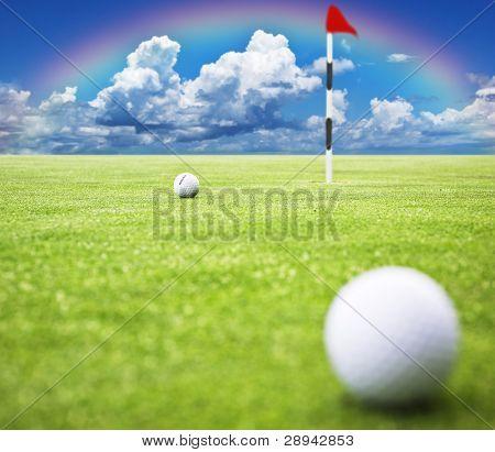 Bola de golfe no verde pronto para ser tacada no buraco com um arco-íris no fundo - Danielle muito