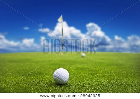 Bola de golfe no verde pronto para ser tacada no buraco