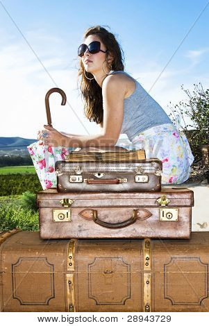 Young traveling woman with her suitcases along the road