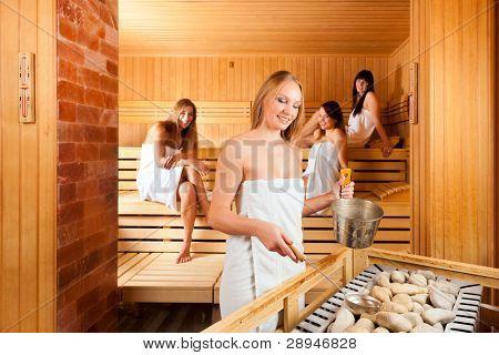 Wellness - jóvenes felices en la sauna de un Spa, el agua y el olor son salpicado de piedras calientes para vapor